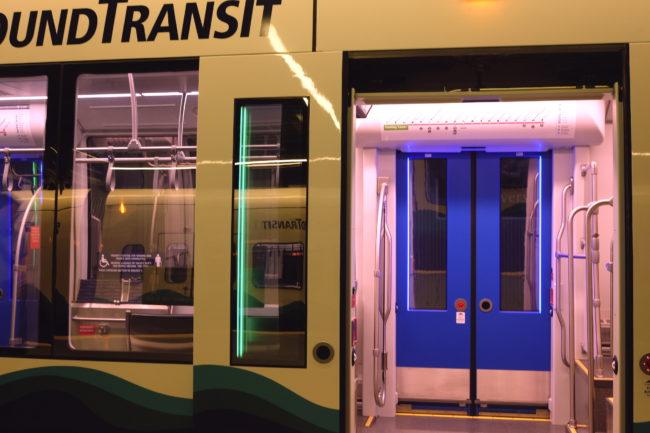 Open door on new Series 2 Link train. Light strips beside the door windows are lit up green. The closed door on the opposite side is lit up blue