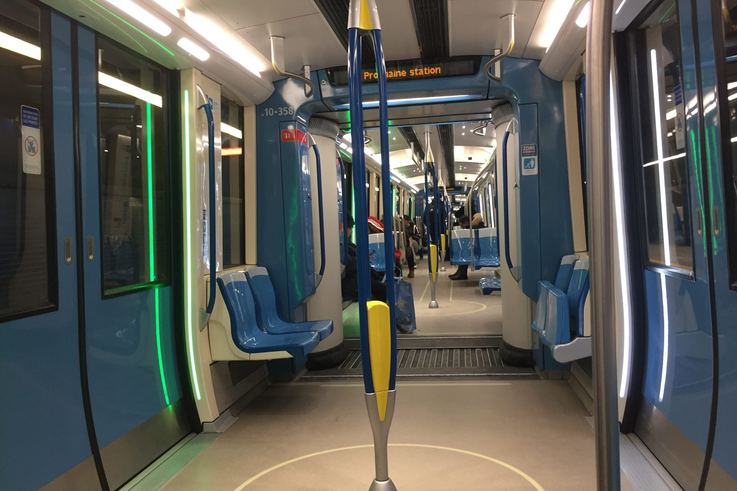 Lights beside the doors on the left are lit in green to indicate they will open at the next station. The doors on the right side of the train are lit in white.