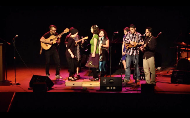 Image of a darkened stage with a folk band of six with various stringed instruments and 2 clog dancers.