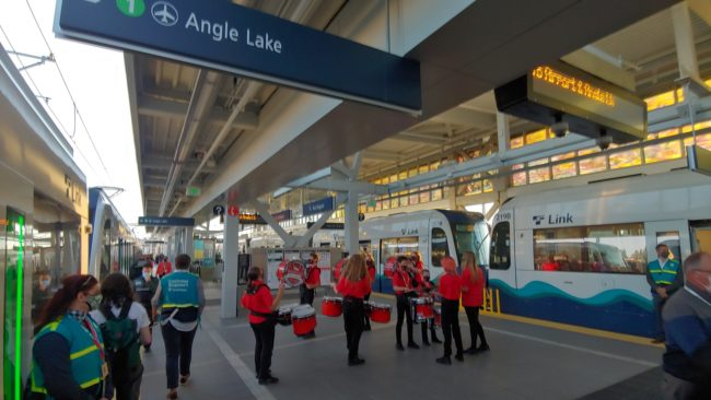 marching drummers stand in center of platform