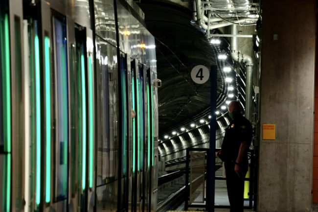 Open doors of train with green lights and downward curvature of tunnel beyond